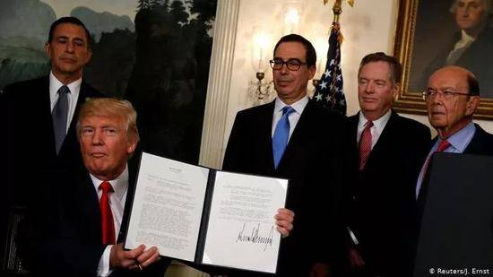 U.S。 President Donald Trump, holds the signed memorandum directing the U.S。 Trade Representative to start the review of trade issues with China at the White House in Washington, U.S。 August 14, 2017。 / Reuters